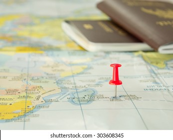 Embroidered red pins on a world map with a passport