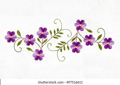 Embroidered satin stitch purple flowers with leaves on cotton cloth