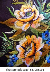 embroidered yellow flowers of roses on natural black fabric, Ukrainian folk embroidery, decorated fabric