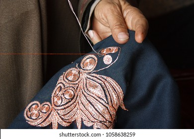 Embroidering a spiral zari design with silver-coated thread on a blue woolen pheran. Srinagar, Kashmir - India. A disappearing artform.