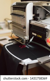 embroidering text on a sewing machine on an industrial scale. machine embroiders the letter f on the fabric. sewing manufacture at the factory.