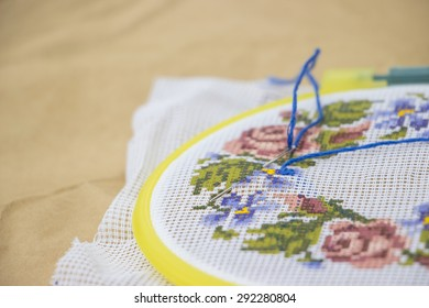 Embroidery with colorful flowers on kraft paper background close up view