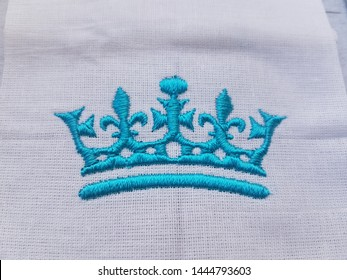 Embroidery crown on the sewing machine, blue thread.
