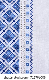Embroidery design by white and blue cotton threads on fabric. Design of ethnic ornament. Background with embroidery texture.
