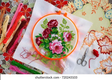 Embroidery of flowers. Embroidery on the frame, as a kind of needlework, creativity and art. View from above. Threads for embroidery, needles, scissors, canvas are needed for embroidery.