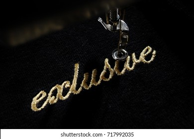 "embroidery of gold lettering ""exclusive"" on black velvety fabric with embroidery machine - top view from left"