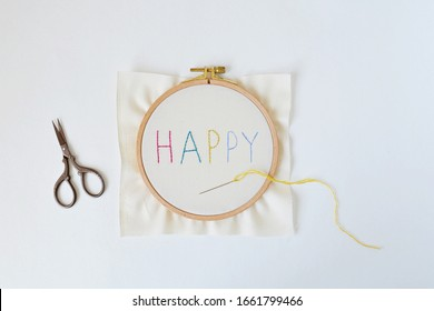 Embroidery hoop with colorful letters, scissors, needle and thread over white