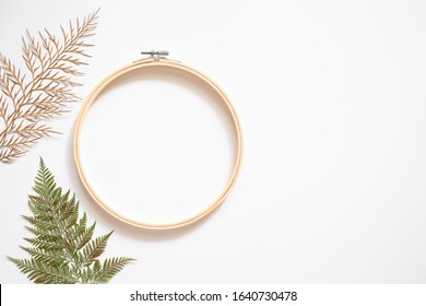Embroidery hoop with dried leafs  on white background