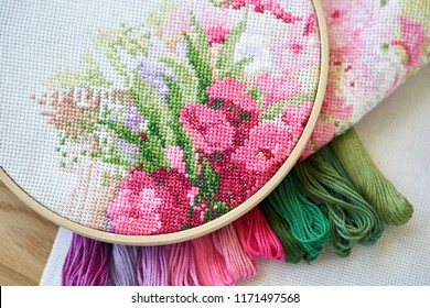 Embroidery hoop with a fragment of  a colorful cross-stitch embroidery and a pile of threads on a wood table.