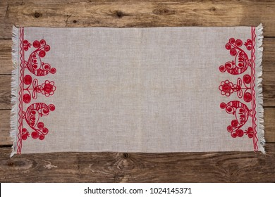 Embroidery linen napkin on the old wooden background. Top view.