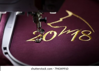 Embroidery with embroidery machine of dog silhouette and number 2018  in gold on claret fabric - chinese new year concept - front view on stitching and hoop