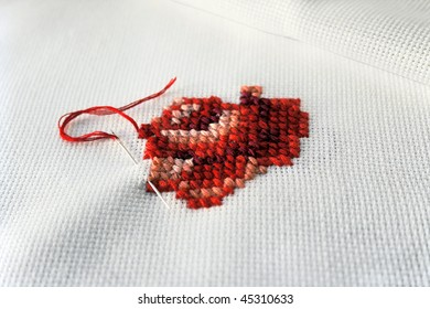 embroidery - a red rose on linen ( macro )