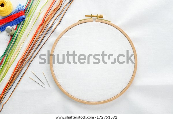 Embroidery set. White linen fabric, embroidery hoop, colorful threads and needls. Copy space.