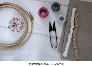 Embroidery tools with hoop, threads, balls, fabric, pin cushion and vintage scissors on the white wood table