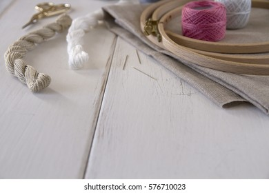 Embroidery tools with hoop, threads, balls, fabric and vintage scissors on the white wood table