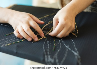 Embroidery with woman hands of flower with beads. Black fabric and Hands. Atelier or Design Studio on tailoring. Close up view.