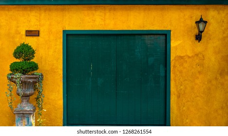 EMBU DAS ARTES, BRAZIL - 26 Dezember, 2018: Green wooden door on a yellow textured colonial wall historic center of Embu das Artes Sao Paulo