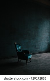 emerald armchair in a classic style on dark textured background. luxury interior in loft. room in deep blue colors