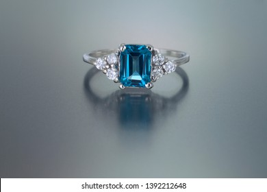 An emerald cut blue topaz is accented by six diamond in this white gold ring.