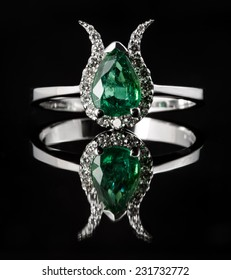 Emerald and diamond engagement ring isolated on black background with reflection