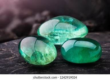 The emerald gemstone jewelry photo with black stones and dark lighting.