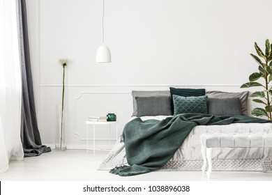 Emerald green bedding on bed with pillows against white wall with copy space in bedroom interior