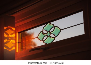 An emerald green beveled top light double glazed window design, catching the glow of a sunset and reflecting onto vertical blinds slats.