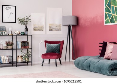 Emerald green futon with pink pillows on the floor against red, ombre wall in elegant living room interior with gray lamp and velvet chair