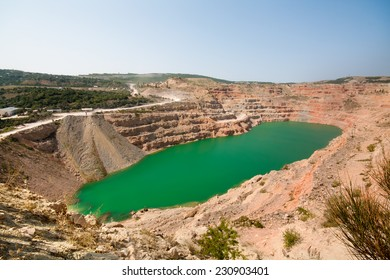 Emerald green lake in flooded opencast mine, open pit. Oval lake in mining industrial crater, acid mine drainage in rock. Open pit mine with lake. Quarry fluxes for the industry.