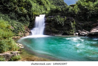 Emerald green waterfall at Du Gia, at the Ha Giang loop in Northern Vietnam. Stunning landscape long exposure photo.