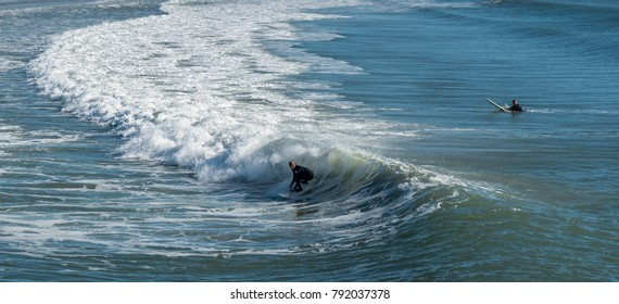 Emerald Isle, NC/US-November 25 2017:surfer riding a wave with foam and surfer in background
