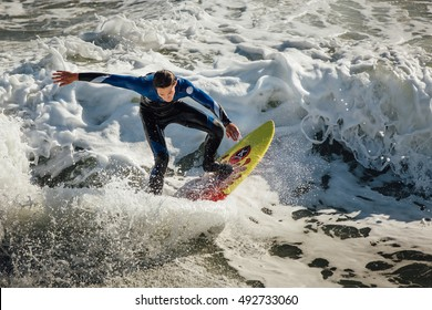 EMERALD ISLE, NORTH CAROLINA - 23 MARCH 2016: A surfer rides a frothy wave