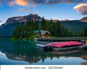 Emerald Lake, Alberta, Canada - June 27, 2017 : Canoes on beautiful Emerald Lake with lake lodge and restaurant in the background in Yoho National Park, Canada.