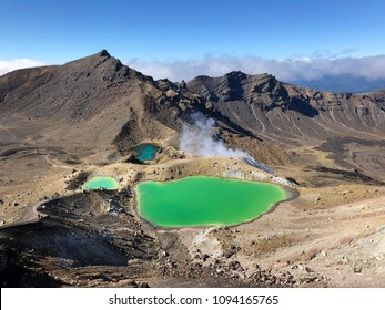 Emerald Lakes at New Zealand's popular Tongariro Alpine Crossing hike with geothermal steam on a sunny day