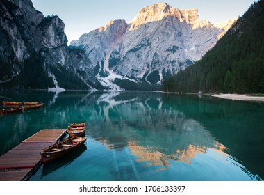 Emerald Mountain Lake Braies. boat station. Wooden pier. Morning landscape in Italy