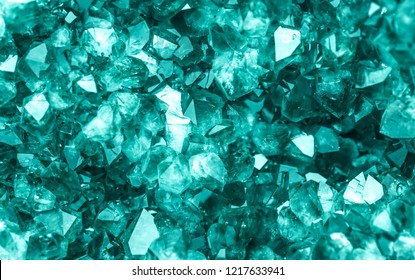 Emerald, Sapphire or Tourmaline green crystals. Gems. Mineral crystals in the natural environment. Stone of precious crystals on white background is insulated. Copy space. Colored shiny bokeh surface.