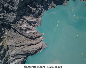 Emerald sulfur lake with yellow sulfur inside the crater of the Mount Ijen volcano in Java, Indonesia
