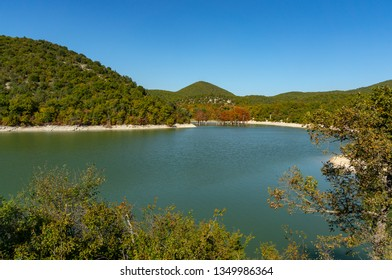 Emerald water of a lake in Sukko, against the background of a mountain covered with forests. Natural beauty of the resort near Anapa. Nature concept for design