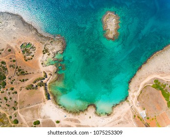 Emerald water at seaside in Italy, top down view. Beautiful aerial view of coastline with rocks and little island. Travel and nature concepts.