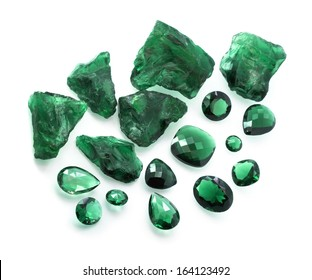 Emeralds collection: many different shapes faceted and raw green gemstones.