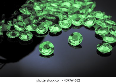 Emeralds scattered on a shiny surface with prominent emerald in the middle
