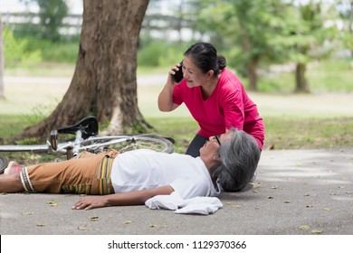 emergency. Asian seniors or Elderly woman using or talking Smartphone call emergency,Help after senior's man heart attack while exercising together in morning with copy space