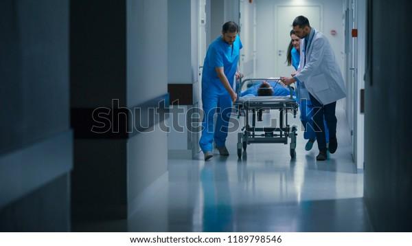 急诊科:医生、护士和护理人员将带重伤病人的担架推向手术室。 明亮的现代医院,拥有专业人员拯救生命。