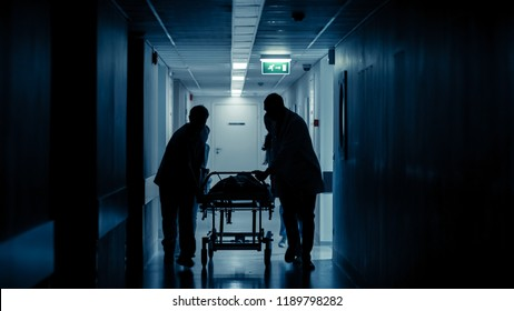 Emergency Department: Silhouettes of Doctors, Nurses and Paramedics Run and Push Gurney / Stretcher with Seriously Injured Patient towards the Operating Room. Modern Hospital with Professional Staff.