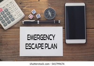 Emergency Escape Plan  written on paper,Wooden background desk with calculator,dice,compass,smart phone and pen.Top view conceptual.