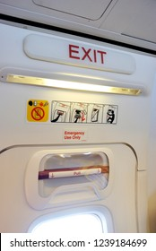Emergency exit door in an airplane with text in English