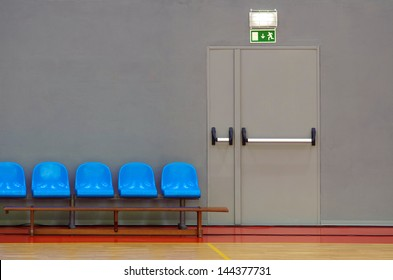 Emergency exit door next to a row of blue sits in a sports pavilion