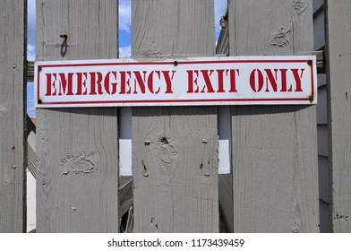 Emergency exit only sign on a wooden door.