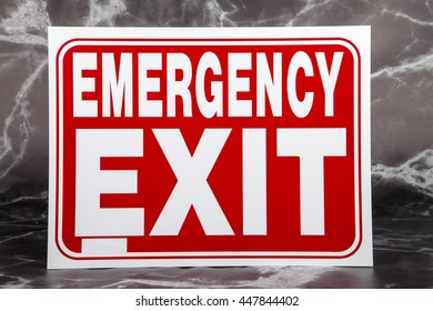 An emergency exit sign against a marble background