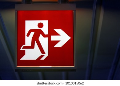 The emergency exit sign shows the direction of escape in case of danger. The emergency exit board hangs on the ceiling of the building.